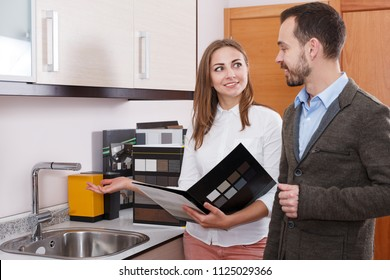Young woman seller consulting man customer in shop of kitchen furnishing and appliances