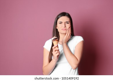 Young woman with sensitive teeth and cold ice cream on color background