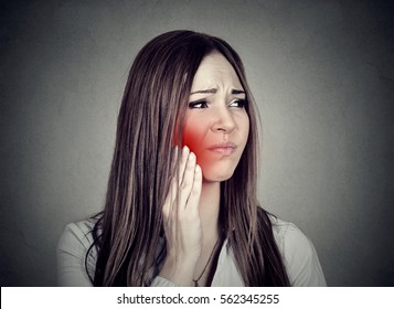 Young woman with sensitive toothache crown problem suffering from pain touching outside mouth with hand isolated on gray background. Negative human emotion feeling