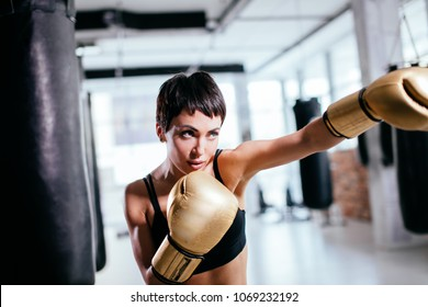 young woman with serious look in yellow sparring gloves fighting indoors. shadow boxing. boxing career