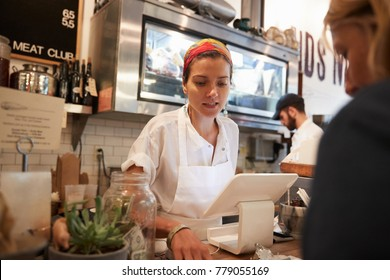 Young woman serving a customer in a butcher's shop