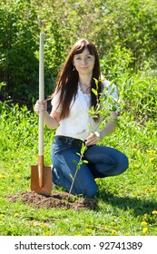 Young woman setting tree outdoor in spring
