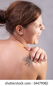 Young woman with sever back pain. She is holding her schoulder. Over grey background. She has a tattoo on her shoulder.