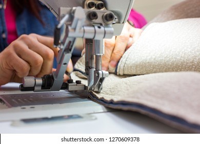 Young woman sewing with industrial sewing machine in textile factory. Close-up.