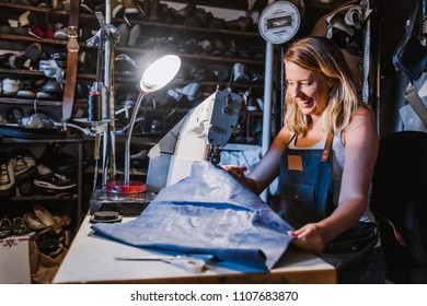 Young woman sewing with sewing machine at studio while sitting at her working place. Fashion designer carefully creating new fashionable styles. Dressmaker makes clothes via additional part-time job.