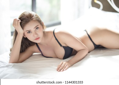 Young woman in sexy black lingerie posing in her bed