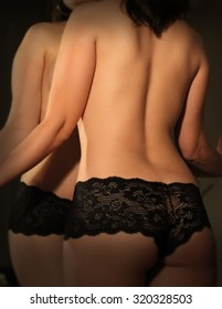 Young woman in sexy black panties face pressed against the mirror