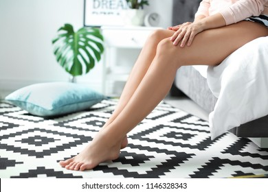 Young woman with sexy legs sitting on bed at home