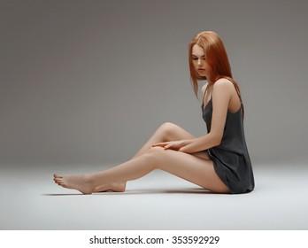 Young woman in sexy underwear on floor studio