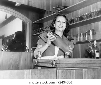 Young woman with a shaker in a bar