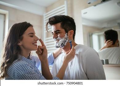 Young woman shaving a man's beard