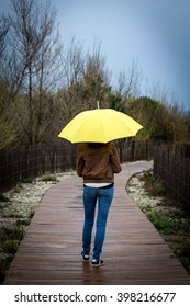 A young woman shelters under a yellow umbrella on a path of wooden beach(range) , vertical frame