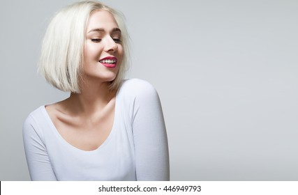 Young woman with shiny blond hair, red lips and pretty smile in white shirt