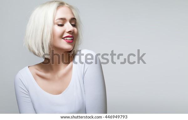 Jonge vrouw met glanzend blond haar, rode lippen en mooie glimlach in wit overhemd