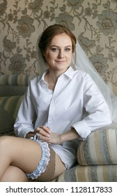 Young woman in shirt with a garter on a foot at home