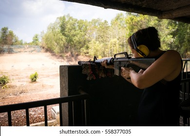 Young woman shooting from a military rifle at a shooting range.