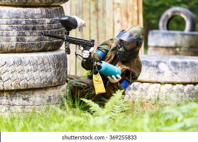 Young woman shooting from paintball gun
