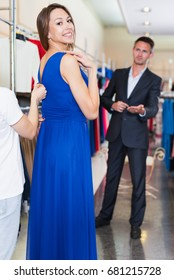 Young woman shop assistant offering dress variants to cheerful pair