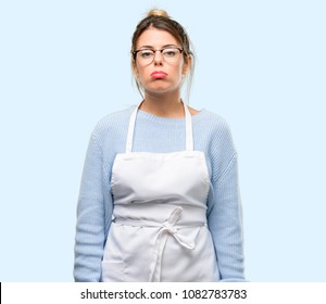 Young woman shop owner, wearing apron with sleepy expression, being overworked and tired