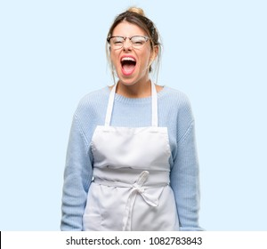 Young woman shop owner, wearing apron stressful, terrified in panic, shouting exasperated and frustrated. Unpleasant gesture. Annoying work drives me crazy