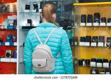 Young woman in shop phototechnique standing near showcase with with photo lenses. Teen girl chooses digital camera. View from the back