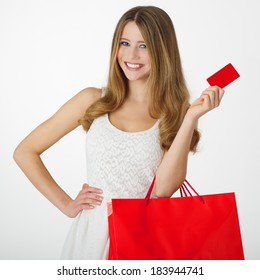 Young woman with shopping bag and card on white background