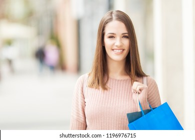 Young woman with shopping bag standing outdoors