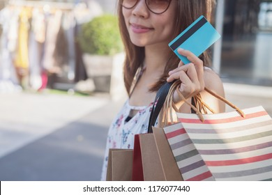 Young woman with shopping bags and credit card at shopping mall on black friday, Woman lifestyle concept