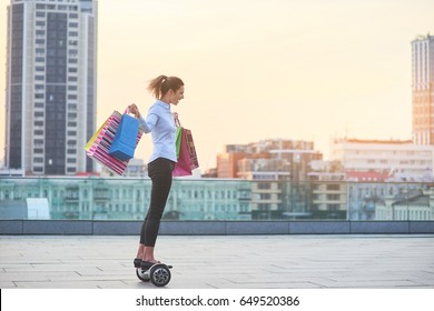 Young woman with shopping bags. Female riding hoverboard.