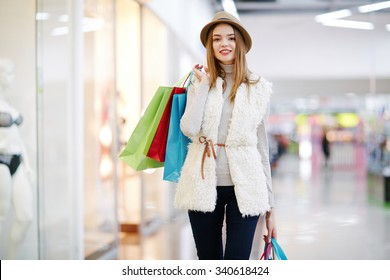 Young woman with shopping bags in mall center