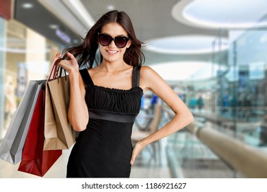 Young woman with shopping bags on blurred background