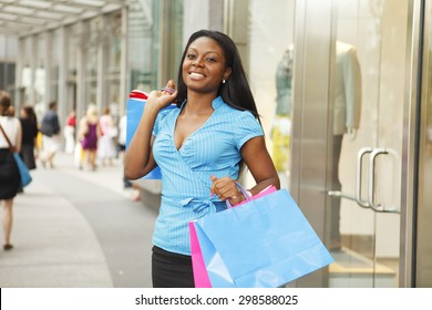 Young woman with shopping bags outside of store.