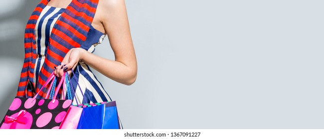 Young woman with shopping bags over grey background