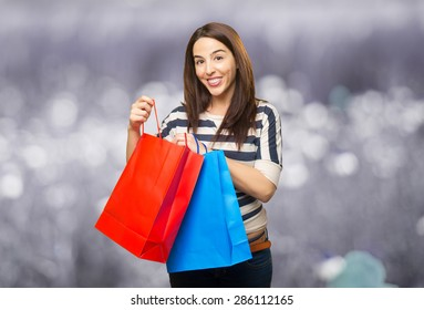 Young woman with shopping bags. Over abstract background