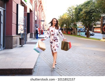 Young woman with shopping bags walking out from shop