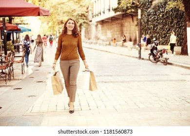Young woman with shopping bags walking on pedestrian street in autumn