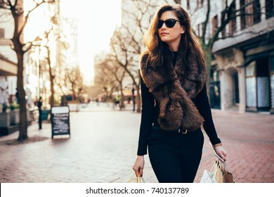 Young woman with shopping bags walking on street. Fashionable female model carrying some shopping bag outdoors on city road.