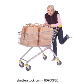 young woman with shopping cart full of papers bags