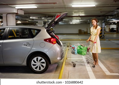 Young woman with shopping cart at underground parking near car with open trunk.