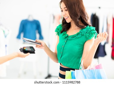 young woman shopping in clothes store and paying by smartphone