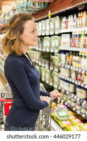 Young woman shopping in the fresh juice section at the grocery store.