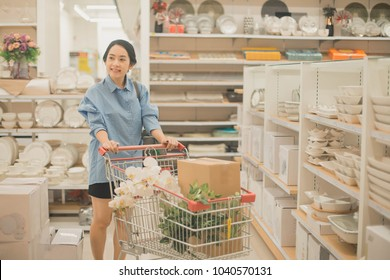 young woman shopping for furniture, glasses, dishes and home decor in store. Woman housewife shopping for furniture, glasses, dishes and home decor, smiling