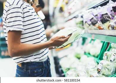Young woman shopping healthy food in supermarket blur background. Female hands buy products cabbage using smart phone in store. Hipster at grocery using smart phone. Person comparing price of produce