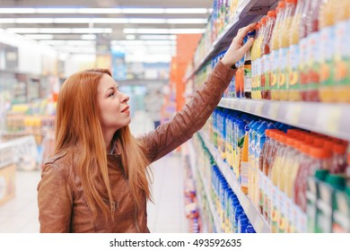 Young woman shopping for juice in a supermarket