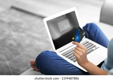 Young woman shopping online with credit card and laptop at home