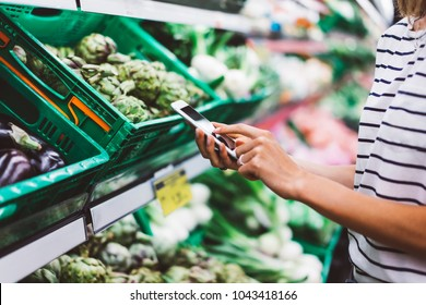 Young woman shopping purchase healthy food in supermarket blur background. Closeup view girl blogger buy products using smartphone in store. Hipster at grocery using smartphone. Person comparing price