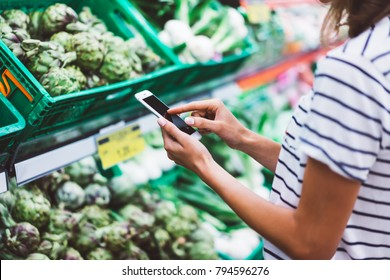Young woman shopping purchase healthy food in supermarket blur background. Close up view girl buy products using smartphone in store. Hipster at grocery using smartphone.  comparing price at store