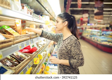 Young woman shopping for recipe ingredients in a large supermarket.Shopping for groceries,household,health and beauty.Self service.Choosing from variety of products and prices