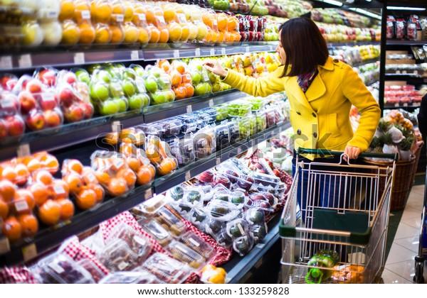 Молодая женщина по магазинам в супермаркете