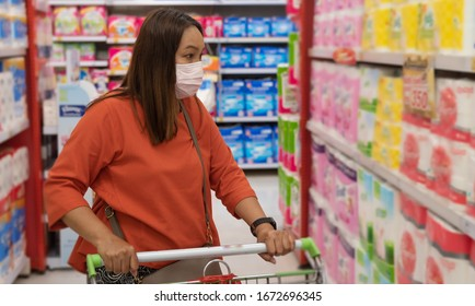 Young woman shopping in supermarket with shopping cart wearing medical face mask to protection the COVID-19 virus.